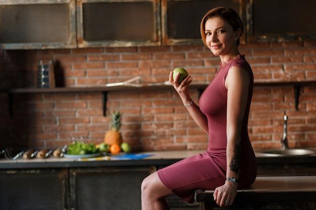 キッチンテーブルに座っているかなりの女性は、リンゴを保持しています。