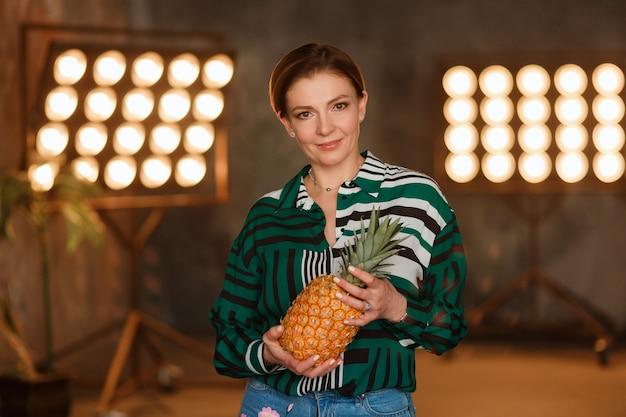 フィットネス、ホーム、ダイエットのコンセプト。キッチンテーブルに立つパイナップルを保持する若い女性