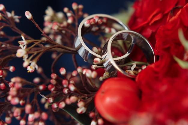 クラシックなホワイトゴールドの結婚指輪、赤い花束