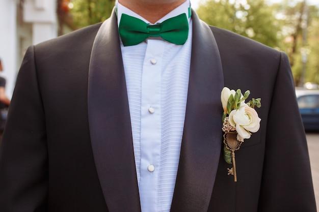 緑色の蝶ネクタイとブートンニエールと新郎のスーツ