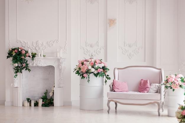 Белый текстильный диван классического стиля в старинном номере. цветы из окрашенных бочек