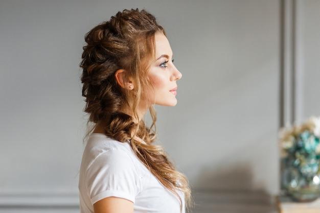 Профиль молодой красивой девушки на фоне серой стены.