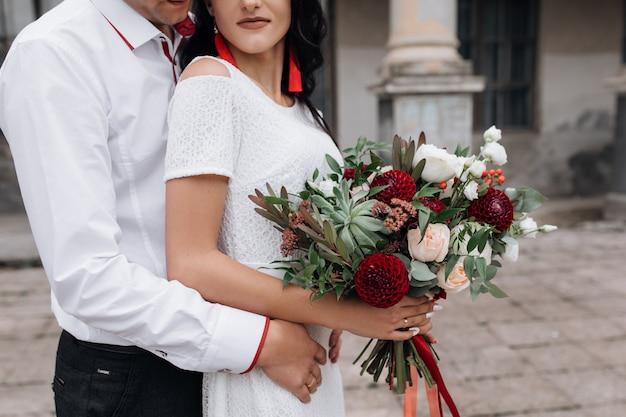 魅力的でスタイリッシュな結婚式のカップルは、古い城の建物の前にポーズ