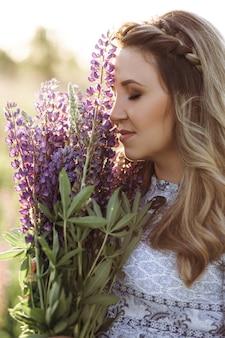 紫のラベンダーの花のフィールドを渡って散歩青いドレスの愛らしいブロンドの女性