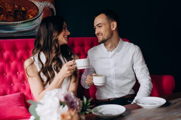 魅力的な若い結婚式のカップルは、明るいピンクのソファに座ってコーヒーを飲む