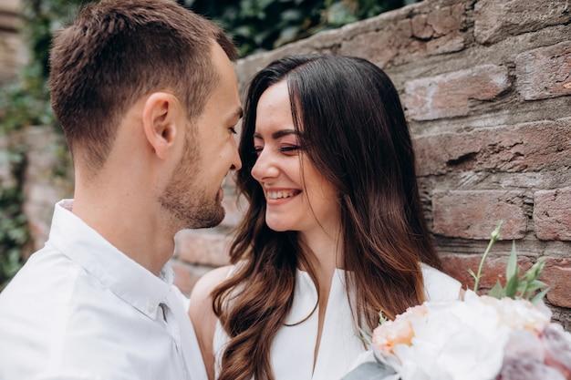 男性と女性は結婚式の日に通りに立って互いをキス