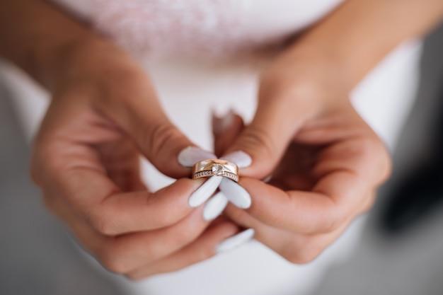 女性は彼女の腕に貴重な結婚指輪を保持しています