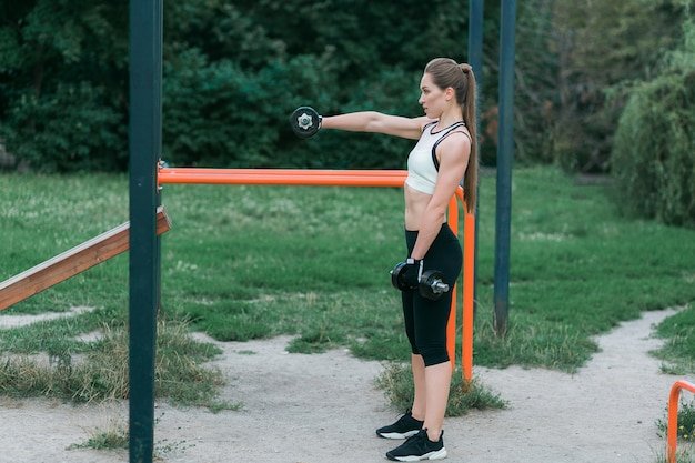 ダンベル、公園で屋外の運動と美しい笑顔の女の子の肖像画。