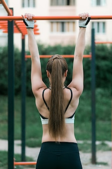 Спорт молодая брюнетка женщина в спортивной одежды вытащил на бар на открытом воздухе.