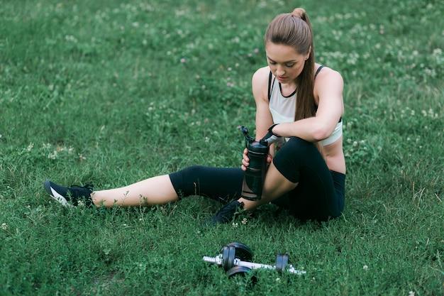 Усталая молодая женщина после тренировки опирается на зеленую траву