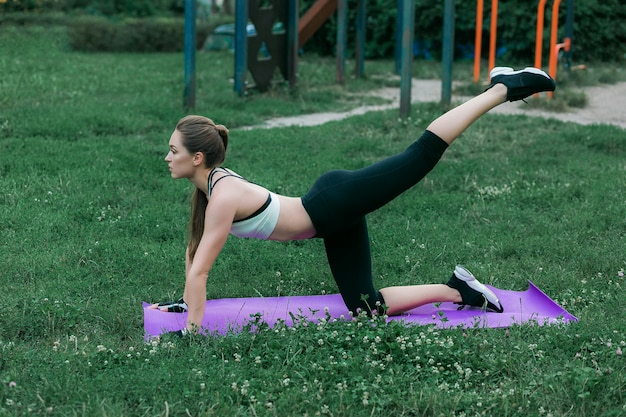 紫色のヨガマットに春の公園で屋外運動フィットネス若い女性