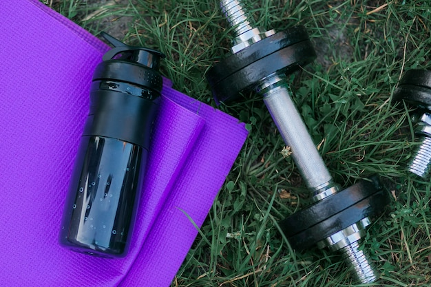 紫のヨガマット、水のボトルと緑の草の上に黒いダンベル。