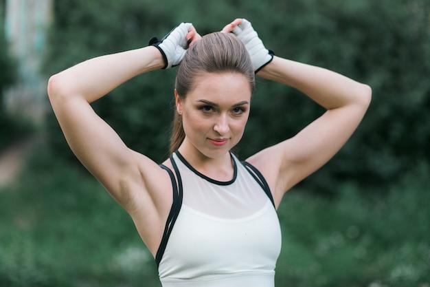 かなり若い女性が緑色の裏庭で運動する前に彼女の髪を固定する