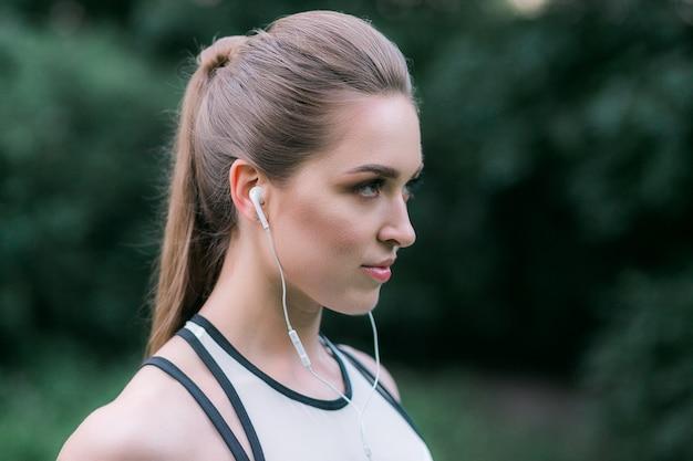 女性の競技者はイヤホンを着用しています。屋外で運動中に音楽を聴く女性。