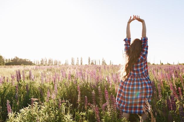 日没の間に花畑で歩く美しい若い女性は、夏の光のドレスを着る。
