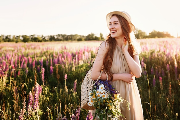 夕日の花畑で歩く幸せな若い女の子。花がいっぱいの麦わら帽子と袋を着て。