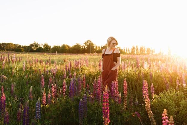 日没時に野生の花畑で歩いている現代のヒップスターの少女。