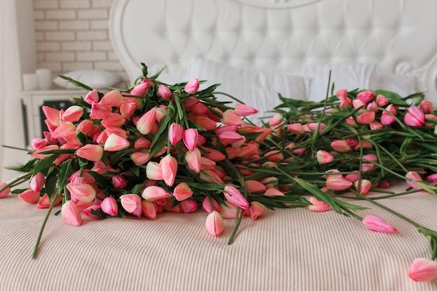 古典的なベッドにピンクの美しい結婚式のチューリップ、クローズアップ