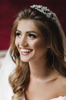 白い絹のローブの美しい花嫁はホテルの部屋のベッドに座っている
