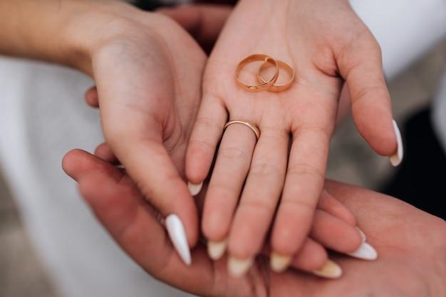 花嫁と新郎は上品な黄金の結婚指輪を腕に持っています