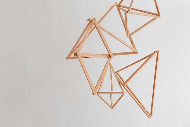 白い壁の背景に隔離された天井から垂れた木製の幾何学的な装飾。