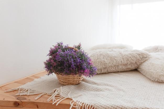 紫色の花の木製の床、ニットの枕とカバーでジュートのバスケット