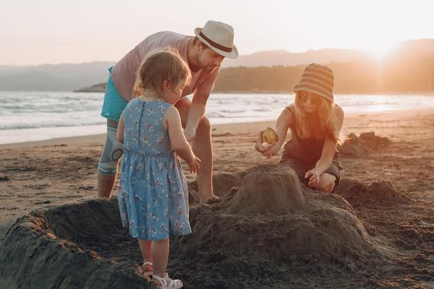夕日のビーチで一緒に楽しむ幸せな家族。建物の砂の城