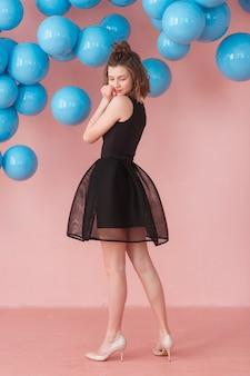 ピンクの壁と青い風船の背景にポーズを取る十代の少女。