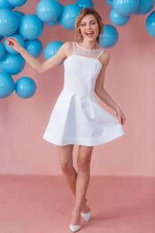 Счастливый девочка-подросток в белом платье, танцы один на ее день рождения.