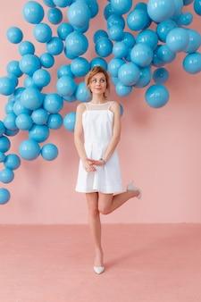 ピンクの背景に踊っているかわいい白いドレスでハッピー笑顔の女の子
