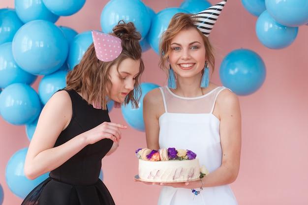 ケーキを持っているパーティーの帽子で二十代の女の子。ピンクの背景と青い風船で分離