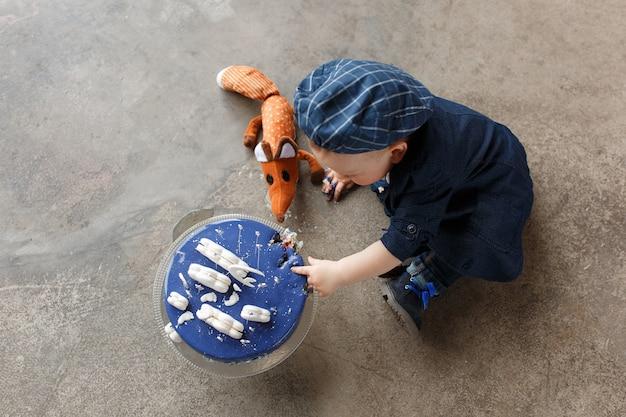 赤ちゃんの男の子の最初の誕生日ケーキの破砕、コンクリートの床の背景の上に