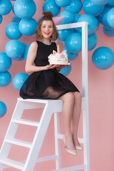 ユニコーンを身に着けている幸せな十代の少女は、メレンゲで飾られたケーキを階層化しました