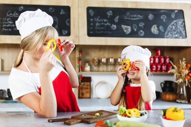 ママと娘は夕食のためにさまざまな野菜を料理するキッチンで楽しい