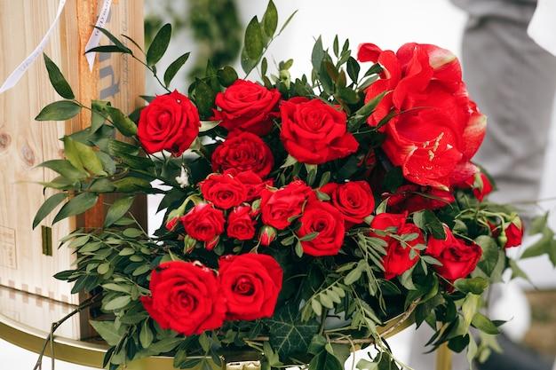赤いバラでできた豊かな花束が外に立つ