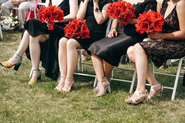 黒いドレスの女性は、赤いユリの花束を保持
