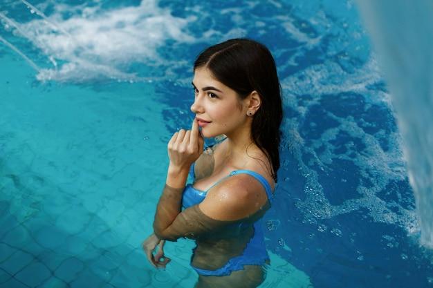Сексуальная девушка стоит в бассейне