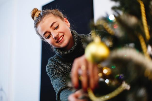 クリスマスと新年の雰囲気。セーターの魅力的な若い女性は準備をしなさい