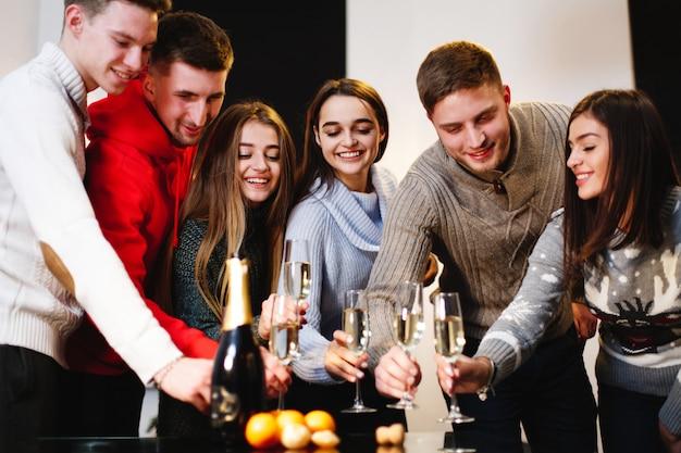 クリスマスと新年の準備。魅力的な幸せな若者の会社が祝う