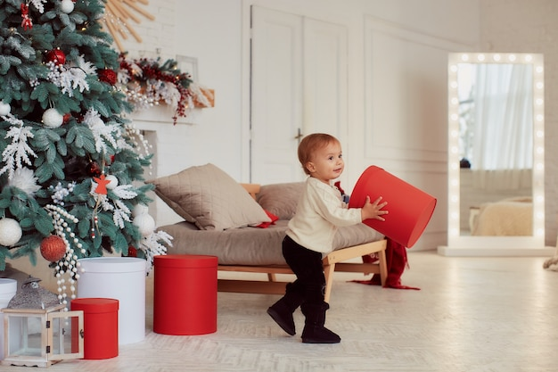 Зимние праздничные украшения. теплые цвета. красивая маленькая девочка играет с подарками