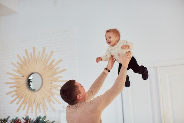家族写真。幸せな父は居心地の良い部屋に立っている彼の腕の中で幸せな女の子を保持します。
