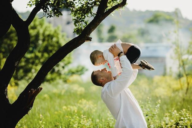 お父さんは緑の木の下に立っている彼の腕に刺繍のシャツで幼い息子を保持します。