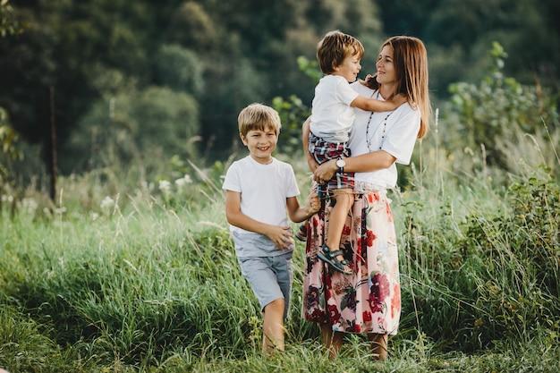 魅力的な若い母親は小さな息子と一緒に歩いています