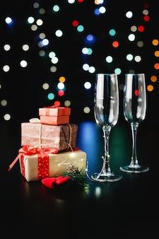 新年とクリスマスの装飾。シャンパンフルート、小さなプレゼントと緑の枝