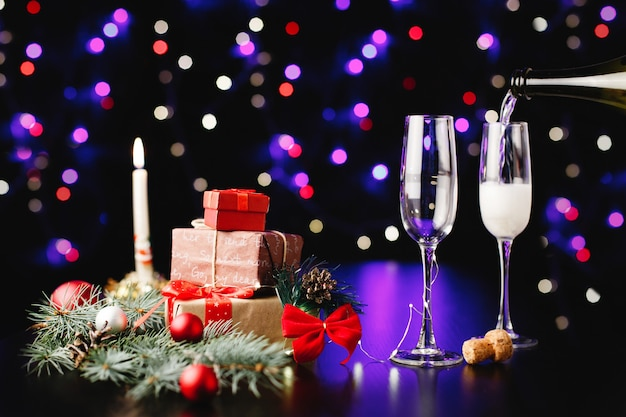 新年とクリスマスの装飾。誰かがグラスにシャンパンを注ぐ