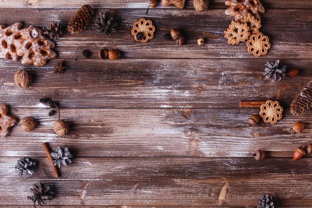 クリスマスの装飾とテキストのための場所。クッキー、シナモンの枝そして円錐形が輪を作る