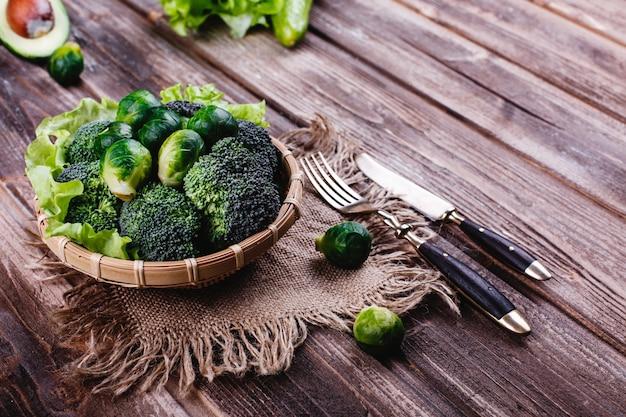 新鮮で健康的な食べ物。ブロッコリー、芽キャベツ、オリーブオイル、ピーマンの木製ボウル