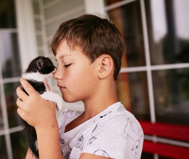 小さな男の子は彼の肩に黒と白の子猫を保持します。