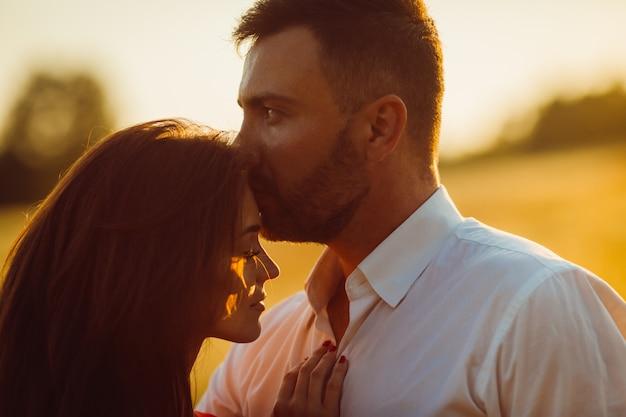 ハンサムなひげを生やした男が黄金の夏の畑で女性の頭の柔らかい地位にキス