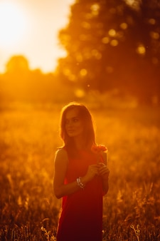 黄金の夏の畑に立っている赤いドレスのゴージャスな女性の写真